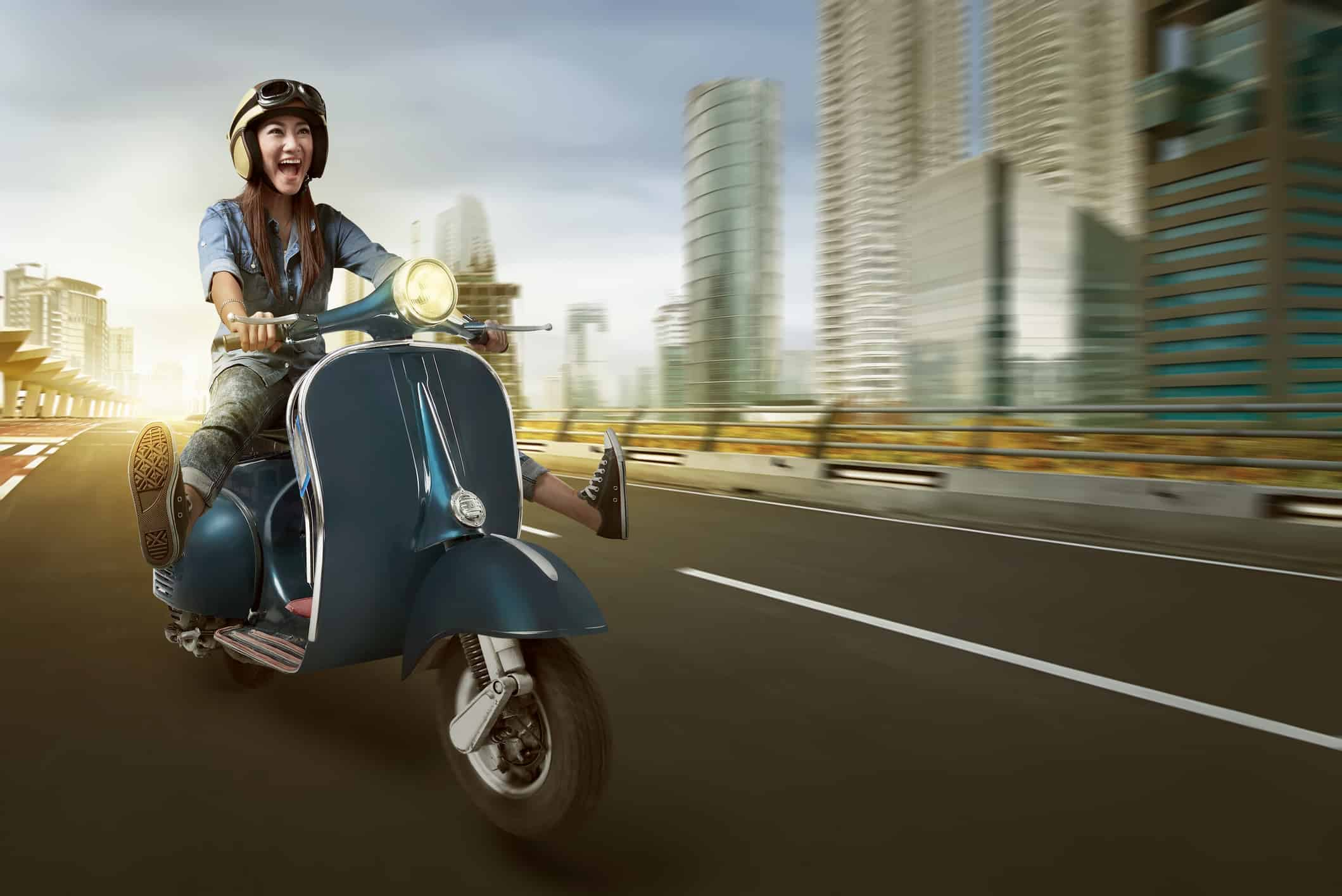 Woman riding motorcycle with big grin on face